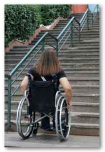 Woman in wheelchair looking at stairs.
